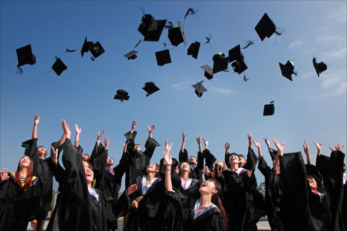 Studenten met hun uitreikingskappen in de lucht